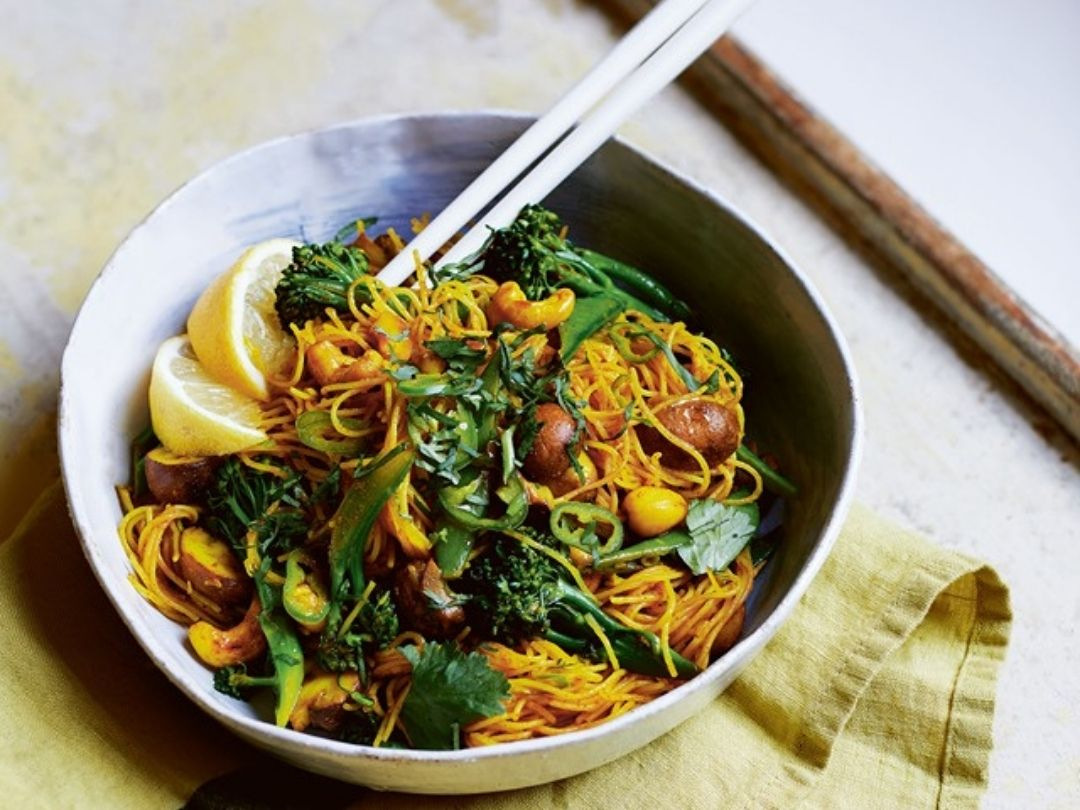 Bowl of Singapore noodles with cashew nuts and broccoli, served with lemon wedges. Recipe from Vegan Fakeaway by Katy Beskow.