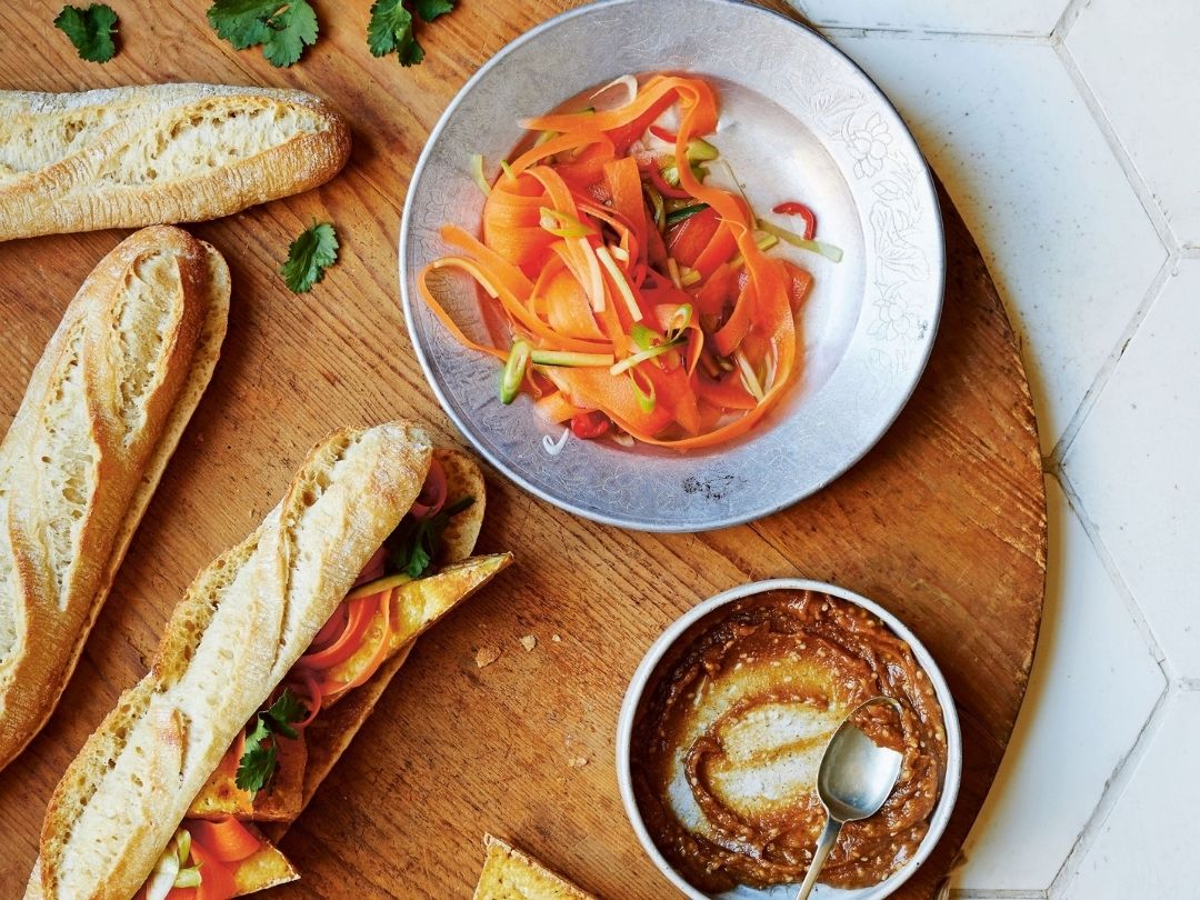 Banh mi with quick pickles from Easy Vegan Bible by Katy Beskow. Photo shows a large wooden serving board topped with baguettes filled with fried tofu, pickled vegetables and a peanut sauce