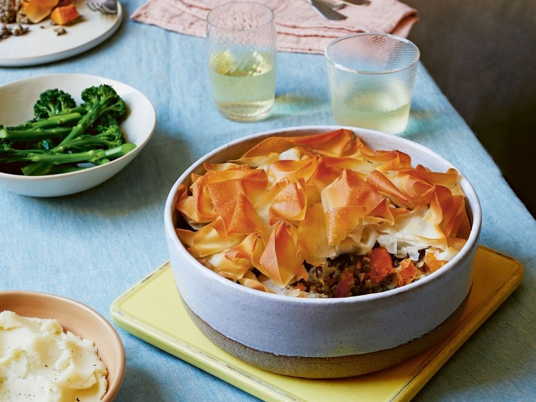 Photo of creamy squash and puy lentil filo pie from Easy Vegan Bible book by Katy Beskow. Photo shows filo topped pie in a round dish with broccoli and mashed potato side dishes arranged on a table with a blue table cloth