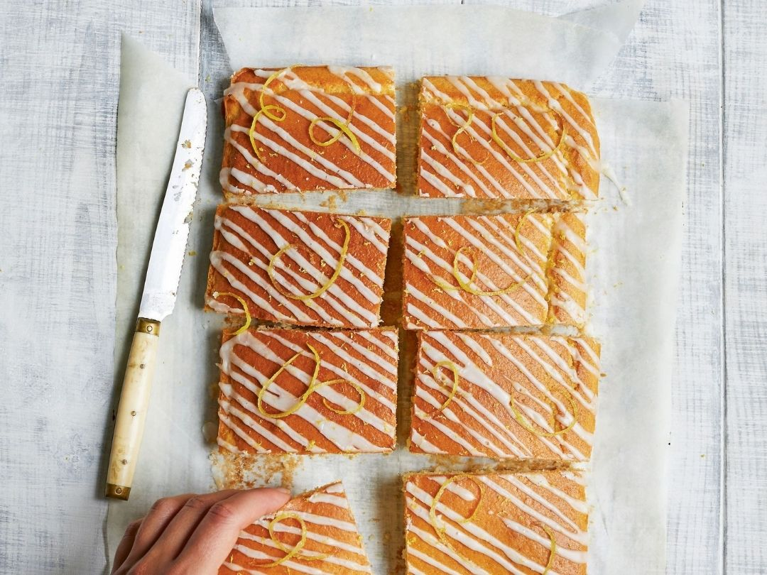Lemon drizzle squares from Easy Vegan Bible book by Katy Beskow. Photo shows eight pieces of lemon drizzle cake on top of baking paper with a knife to the side